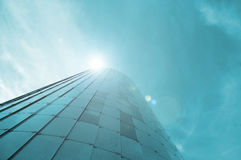 Low view image. Modern glass building skyscrapers over blue bright clear sky with sunlight. Royalty Free Stock Photos