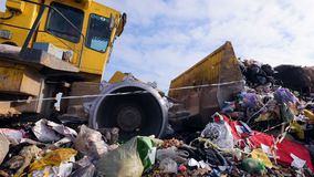 Enviromet pollution concept. A low angle view on a landfill compactor moving trash. A low view on a landfill truck moving a large garbage pile away stock video