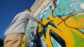 A low view on a man restoring a graffiti painting. A male graffiti artist restores his painting in a low angle view stock video footage