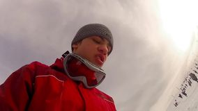 Low view of skier boy with mask and hat stock footage
