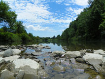 Low view of summer river walking on river rocks with blue sky. Centered image view of water at ground level in river with river rocks in foreground. Green trees royalty free stock image