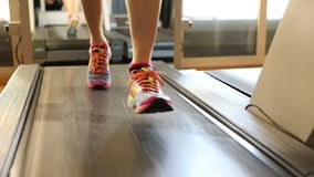 Low view of treadmill run. Healthy lifestyle concept. Slow motion close up. Woman feet in colorful shoes running on treadmill machine in gym. Fitness center stock footage