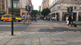 Typical london street with yellow taxi stock images