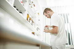 Low view of young pharmacist preparing medicine. In lab. He is mixing ingredients to creative final medicine. Color toned image stock photography