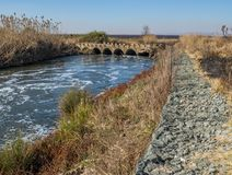 Low water bridge with a gabion retaining wall. Old low water concrete bridge with a modern gabion retaining wall to control erosion image with copy space in stock image