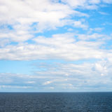 Low white clouds in blue sky over Baltic Sea Royalty Free Stock Photo