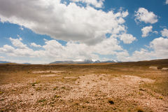 Low white clouds floating over dry land in Central Asia Stock Photo