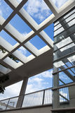 Pergola & Elevator Shaft Architecture. Low & wide angle view of a large pergola and a glass elevator shaft Stock Photos