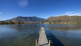 Low wooden jetty in Frankton, near Queenstown, Otago, South Island, New Zealand. Clear lake water and clear blue sky with mountain on the background Royalty Free Stock Photo