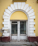 Low wooden window, with white around the arch windows and cracked yellow wall. stock photos