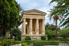 Lowe Barrakka Gardens. View of Lower Barrakka Gardens with historical monumental columns in Malta, with small trees around, on cloudy blue sky background Royalty Free Stock Images