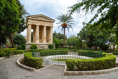 Lowe Barrakka Gardens. View of Lower Barrakka Gardens with historical monumental columns in Malta, with small trees around, on cloudy blue sky background Stock Photos