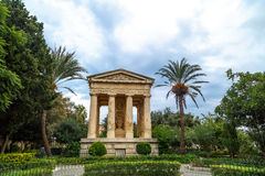 Lowe Barrakka Gardens. View of Lower Barrakka Gardens with historical monumental columns in Malta, with small trees around, on cloudy blue sky background Stock Images