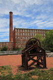 Lowell,Massachusetts, a historic city. Wheel from a historical mill is a landmark in Lowell, Massachusetts, a renovated mill building in the background Stock Image