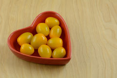 Lower acidic yellow cherry tomatoes. In red heart shaped bowl on wooden table stock photos