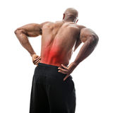 Lower Back Pain. Fit man or athlete reaching for his lower back in pain with the painful area highlighted in red stock images