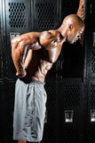 Lower Back Pain. Portrait of a muscle fitness man reaching for his lower back in pain Royalty Free Stock Image