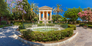 Lower Barrakka Gardens, Valletta, capital of Malta. Panorama of blossoming spring Lower Barrakka Gardens and monument dedicated to Alexander Ball in the old town Royalty Free Stock Images