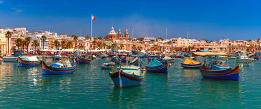 Lower Barrakka Gardens, Valletta, capital of Malta. Panorama with raditional eyed colorful boats Luzzu in the Harbor of Mediterranean fishing village Marsaxlokk Stock Photo