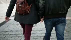 Lower bodies of young dating couple holding hands