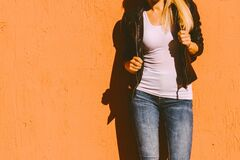 Free Lower Body Of Young Woman In White T Shirt Black Leather Jacket And Blue Jeans Lean On Yellow Wall In City Summer Day Stock Photo - 184187070