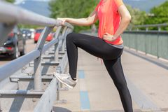 Lower body of a slender athletic woman. In sportswear standing on a pedestrian walkway facing a motorway with traffic royalty free stock image