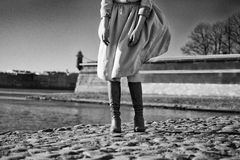 Lower Body of woman dressed in a coat and boots, standing on the Stock Images