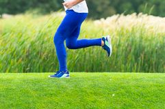 Lower body of a woman sprinting through a park stock image