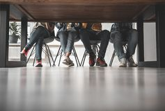 Student legs in jeans and snickers. Lower body of young people sitting at the table. They are wearing casual clothes and sport shoes. Low angle. Copy space Royalty Free Stock Photography