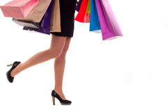 Lower close-up, running girl holding shopping paper bags and pac Stock Image