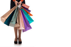 Lower close-up, woman stands holding shopping paper bags and pac Stock Images