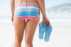 Lower half of fit woman holding flip flops on beach. On a sunny day Royalty Free Stock Photos