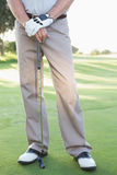 Lower half of golfer standing with club Stock Image