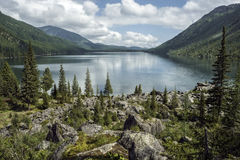 Lake in the mountains surrounded by old trees and large boulders Royalty Free Stock Images