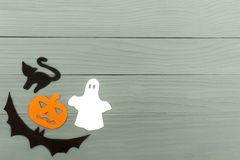 Lower left corner frame of halloween paper silhouettes. Lower left corner frame of halloween with pumpkin, ghost, bat and cat paper silhouettes on a gray wooden Stock Photo