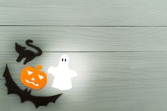 Lower left corner frame of halloween paper silhouettes. Lower left corner frame of halloween with pumpkin, ghost, bat and cat paper silhouettes on a gray wooden Royalty Free Stock Images