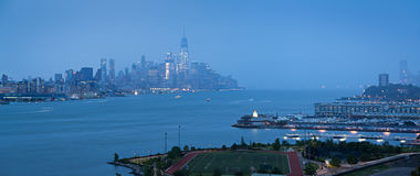 Lower Manhattan with heavy rainfall in evening and Financial District skyscrapers and Weehawken, New Jersey waterfront. New York Stock Photography