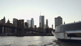 Lower Manhattan-Skyline mit einer Yacht im Vordergrund gefilmt vom Boot im East River unter der Brooklyn-Brücke stock video