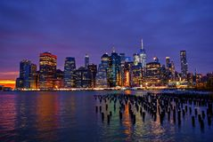 Lower Manhattan skyline at night. Lower East Side Manhattan at night with fiery sunset at background Royalty Free Stock Images
