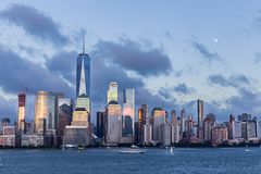 Lower Manhattan-Skyline und -mond, die an der blauen Stunde steigen Stockbilder