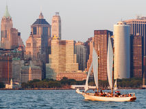 Lower Manhattan at sunset with a sailboat on the bay Royalty Free Stock Photo