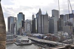 Lower Manhattanpanorama från den Brooklyn bron över East River från New York City i Förenta staterna royaltyfri fotografi