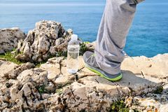 Lower part of a leg on a rock. Mens sportswear, Athletes foot, sweatpants, a sneaker and a bottle of fresh clean drinking water. With a beautiful sea in the royalty free stock images
