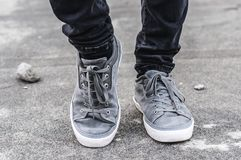Lower part of the male legs in gray sneakers. On the asphalt road Stock Image