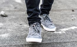 Lower part of the male legs in gray sneakers. On the asphalt road Royalty Free Stock Image