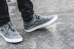 Lower part of the male legs in gray sneakers. On the asphalt road Stock Images