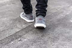 Lower part of the male legs in gray sneakers. On the asphalt road Royalty Free Stock Photos