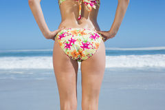 Lower rear view of fit woman in floral bikini at beach Royalty Free Stock Image