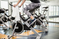Lower section of fit woman on exercise bike Stock Photo