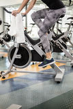 Lower section of fit woman on exercise bike Royalty Free Stock Images